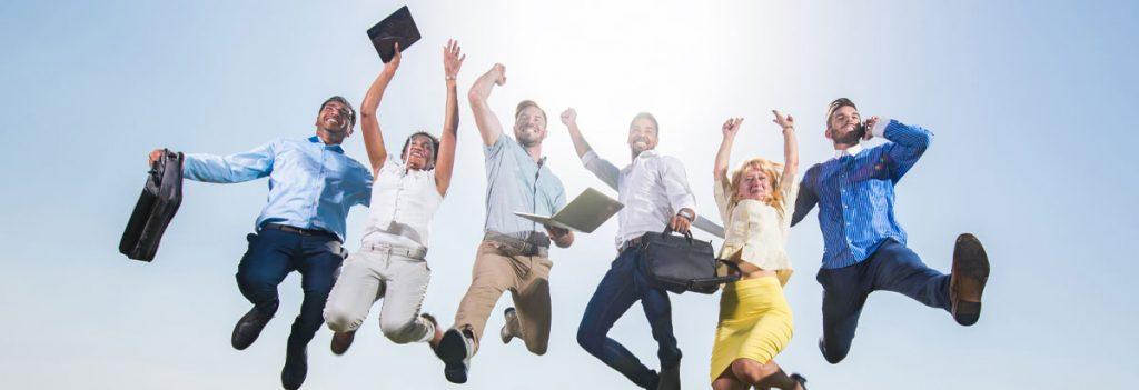 6 Personen, in Businesskleidung, springen in die Luft und freuen sich. Dahinter ein strahlend blauer Himmel