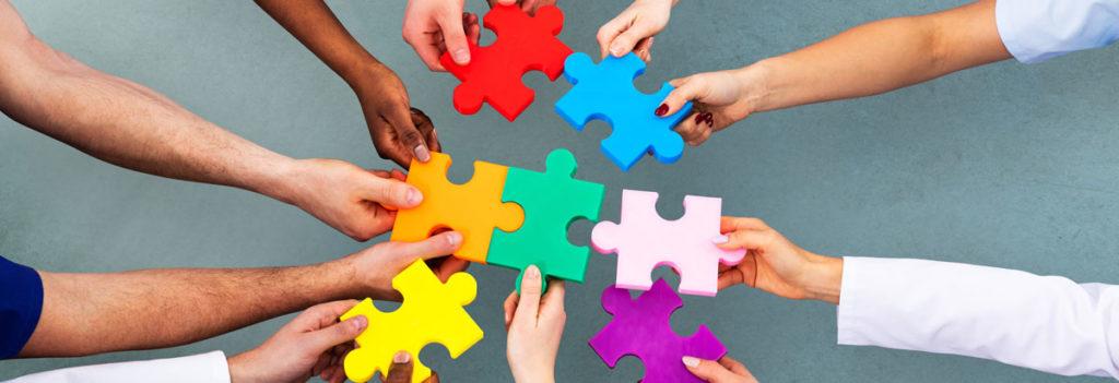 mehrere Hände halten einzelne Handgroße bunte Puzzlestücke in der Mitte zusammen