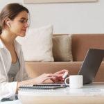 Eine Frau sitz am Laptop und arbeitet
