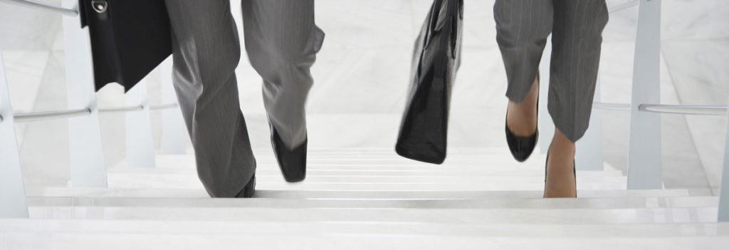2 Personen laufen eine Treppe hoch. Ein Mann und eine Frau in Business Kleidung. Man sieht nur die Füße